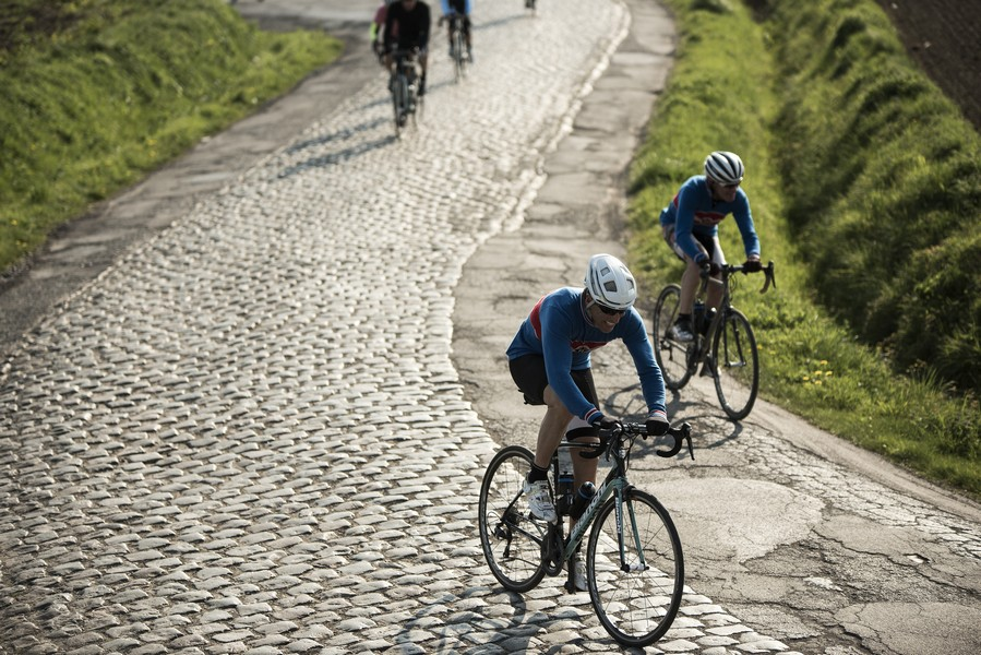 Riders descending steep cobbled road